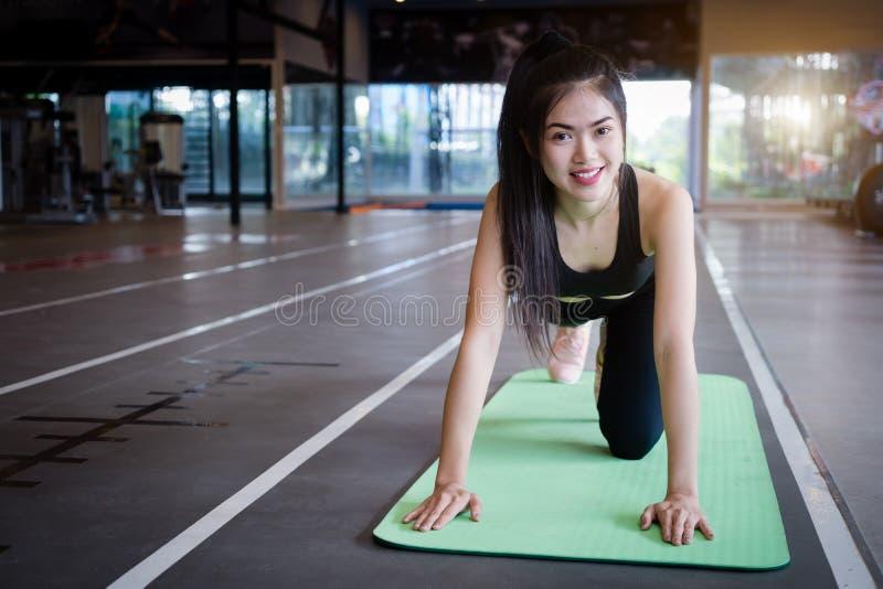 在健身房的美好的亭亭玉立的年轻女人俯卧撑 免版税库存照片