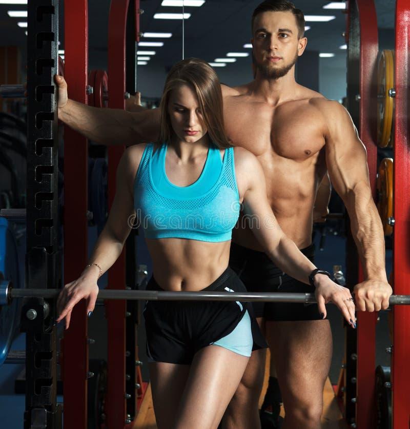 在健身房的美好的年轻运动的性感的夫妇锻炼 免版税库存照片