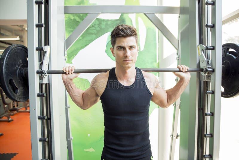 在健身房的英俊的人训练 库存图片