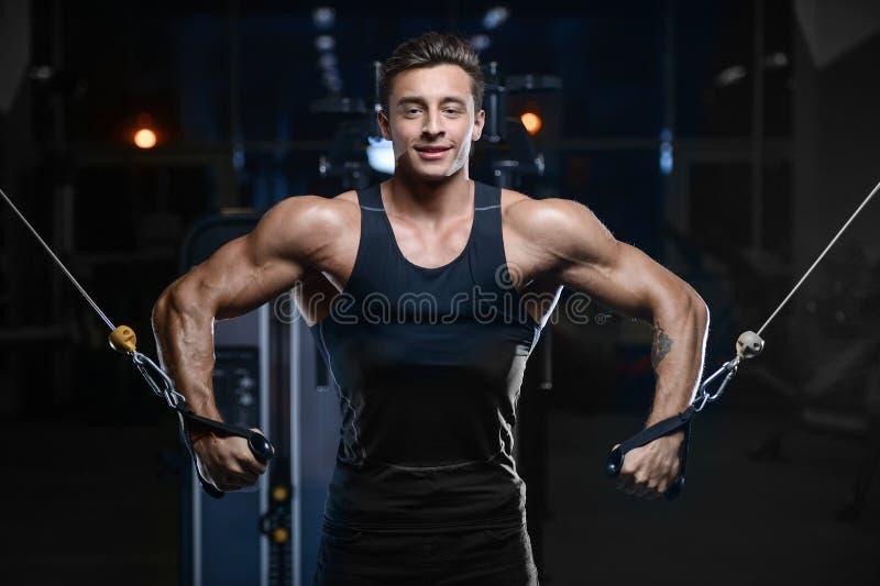 在健身房的英俊的式样年轻人锻炼 免版税库存照片