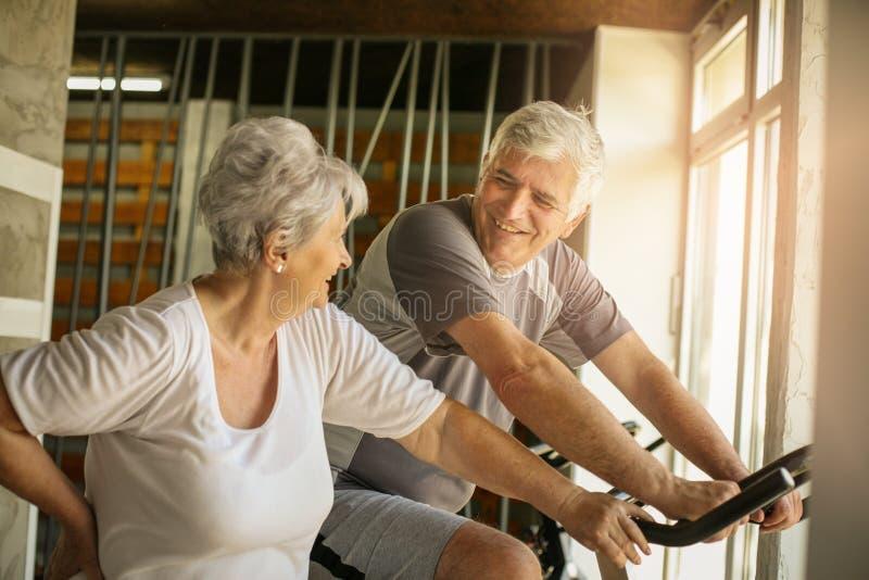 在健身房的资深人锻炼 老人坐 库存照片