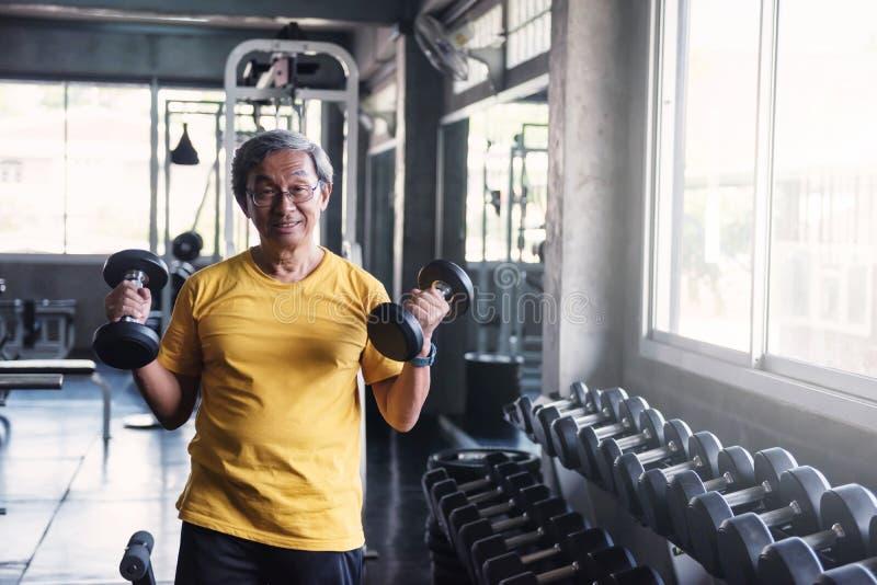 在健身房的资深坚强男人哑铃锻炼 免版税库存图片