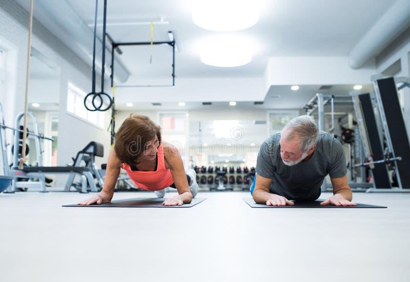 在健身房的资深夫妇在板条安置运作的吸收 库存照片