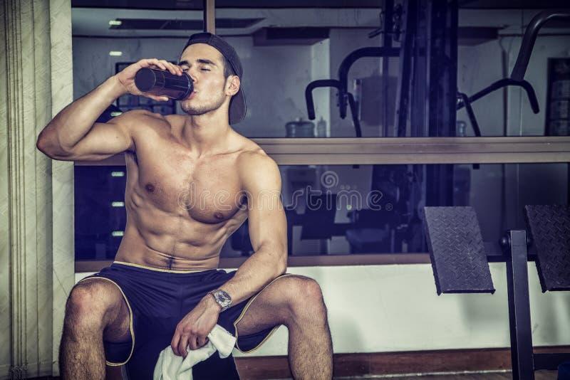 在健身房的赤裸上身的年轻人饮用的蛋白质震动 免版税库存图片