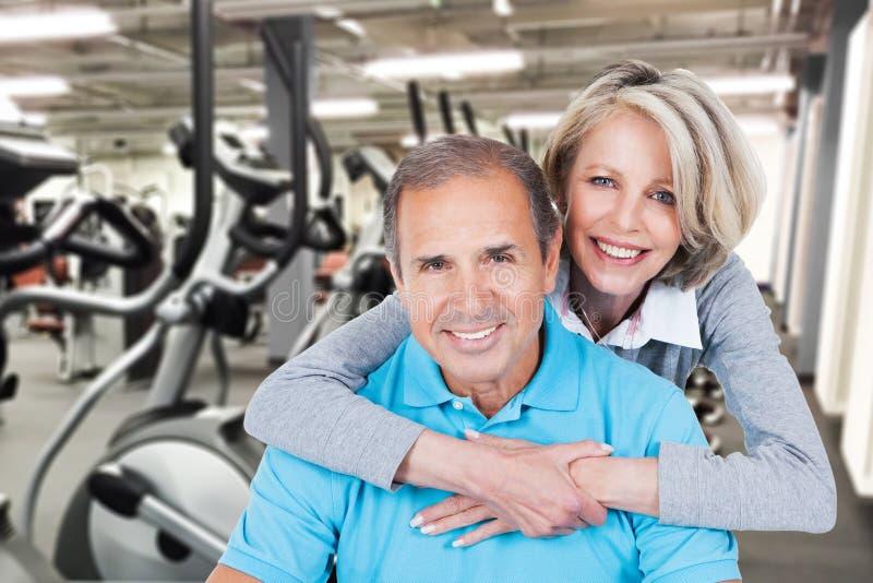 在健身房的适合的成熟夫妇 免版税库存图片