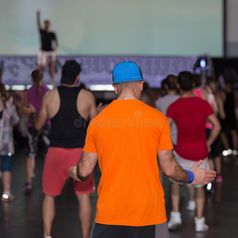 在健身房的锻炼:有帽子的男孩行使与在健身类的音乐的 库存照片