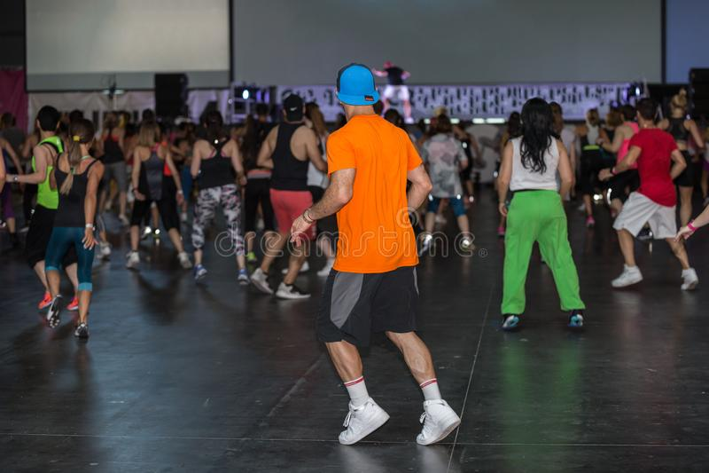 在健身房的锻炼:有帽子的男孩行使与在健身类的音乐的 免版税库存图片