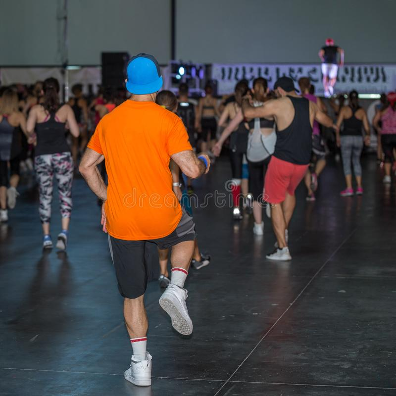 在健身房的锻炼:有帽子的男孩行使与在健身类的音乐的 免版税库存照片