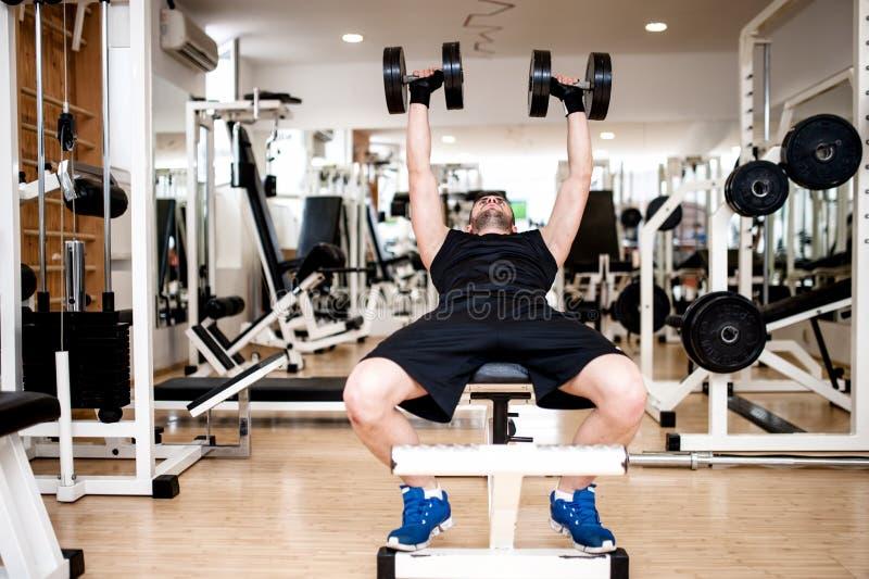 在健身房的年轻人训练与dumbbel 库存图片