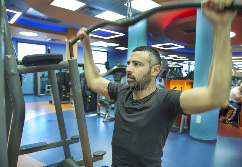 在健身房的年轻人锻炼 免版税库存图片