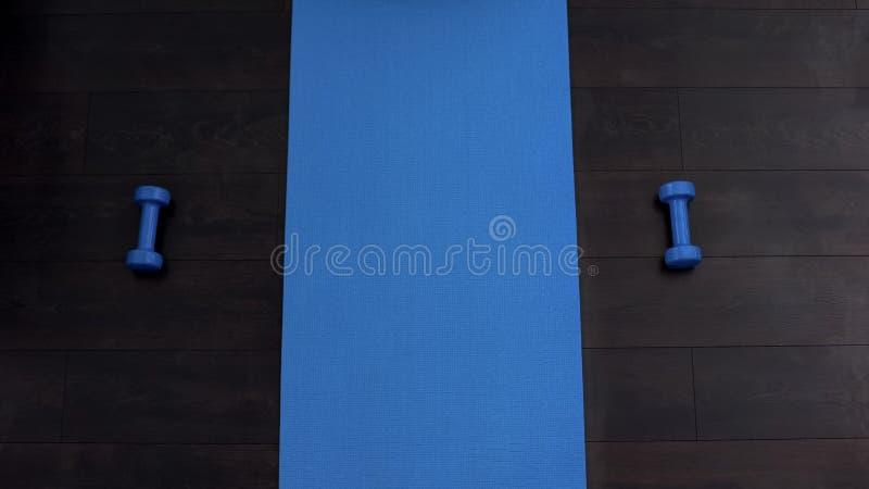 在健身房,哑铃说谎在双方的,训练地板上的空的健身席子  免版税库存照片