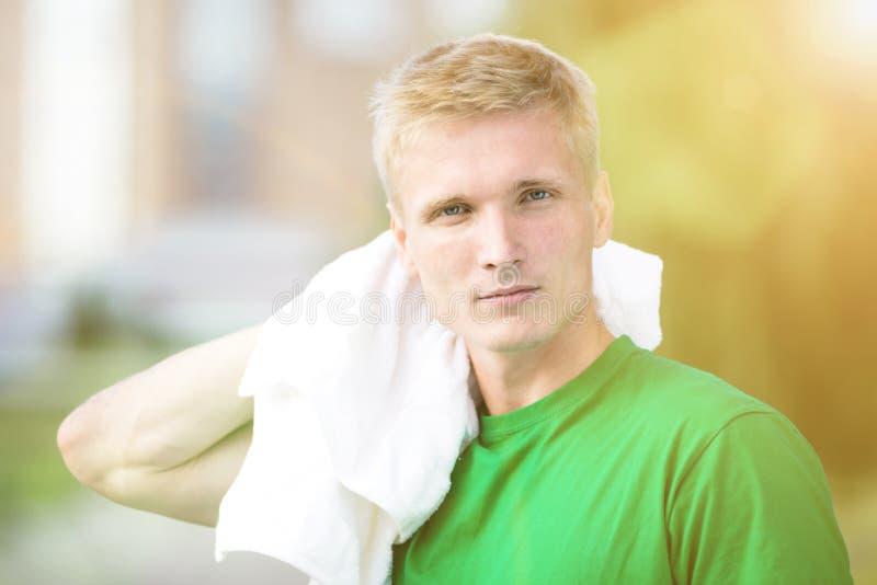 在健身时间和行使以后的疲乏的人 白色毛巾 免版税库存图片