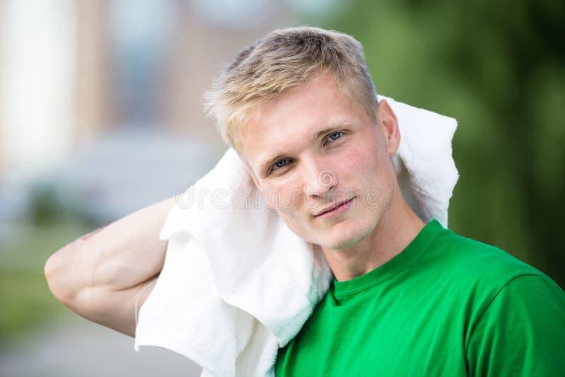 在健身时间和行使以后的疲乏的人 白色毛巾 免版税图库摄影