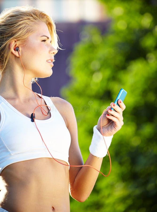 在健身期间的妇女在城市是听到音乐 库存图片