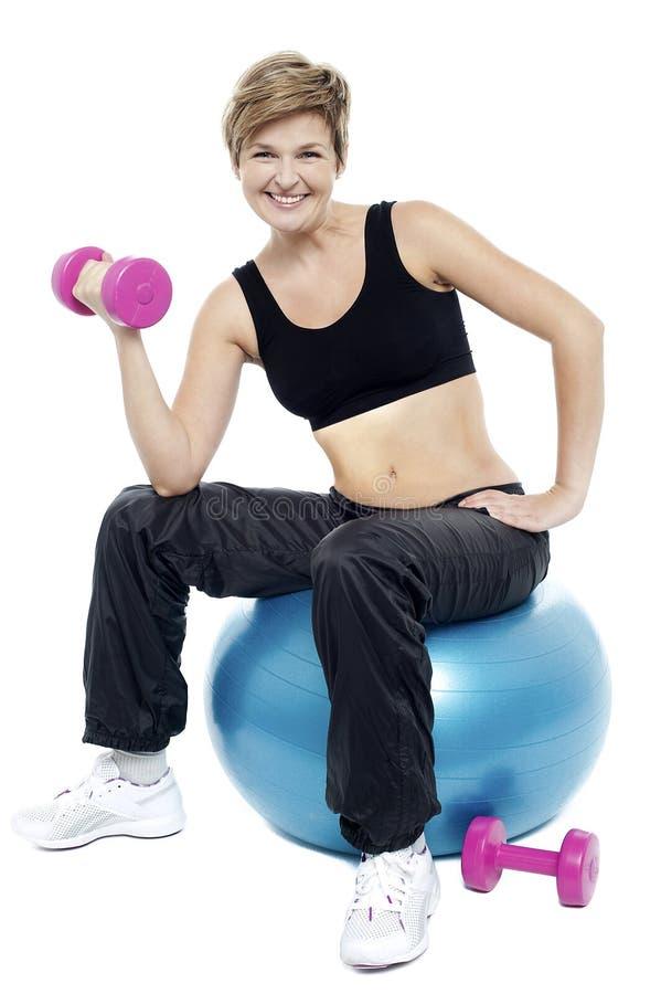 在健身球安装的妇女执行哑铃 图库摄影