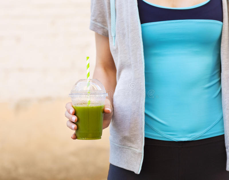 在健身连续锻炼以后的妇女饮用的菜圆滑的人 库存图片