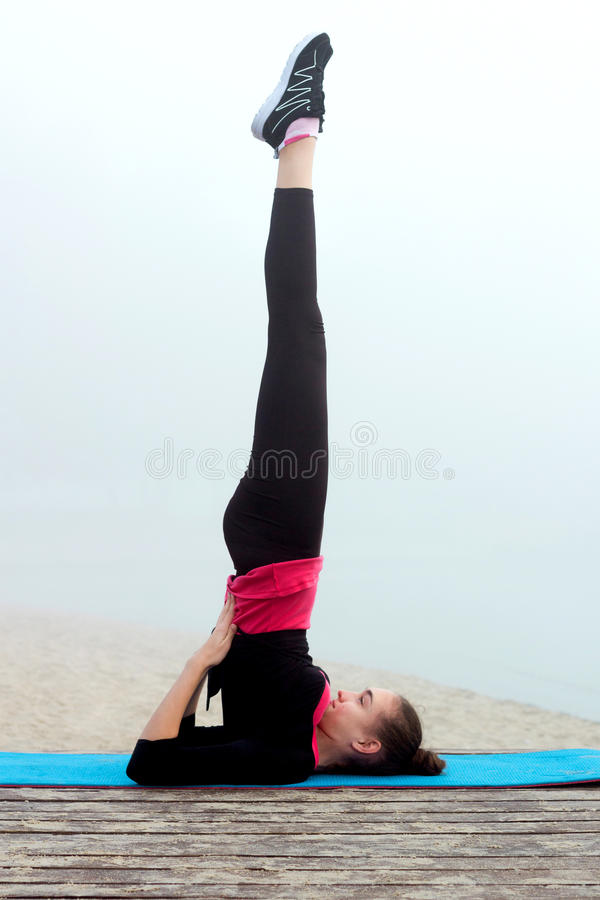 在健身锻炼o期间,做瑜伽的年轻运动的妇女行使 库存图片