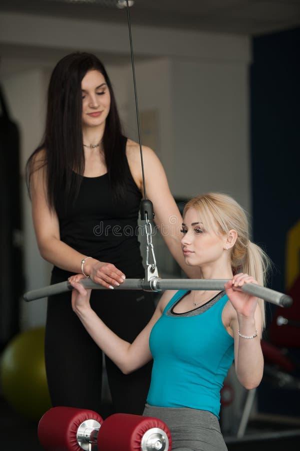 在健身gim的美好的白肤金发的妇女锻炼与做拉扯下来的她的教练行使 库存图片
