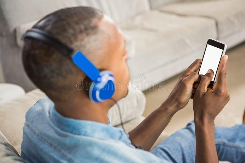 在偶然人听的音乐肩膀视图  免版税库存照片