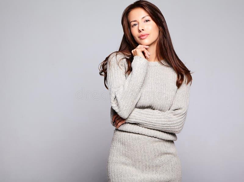 在偶然在灰色穿衣没有构成隔绝的秋天灰色毛线衣的逗人喜爱的深色的妇女模型 免版税库存图片