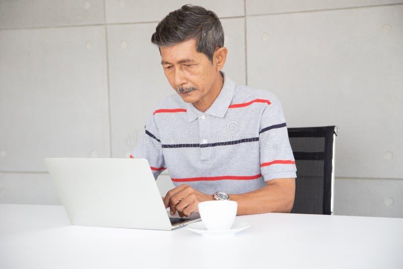 在偶然工作的资深亚洲商人在用途膝上型计算机旁边 库存图片