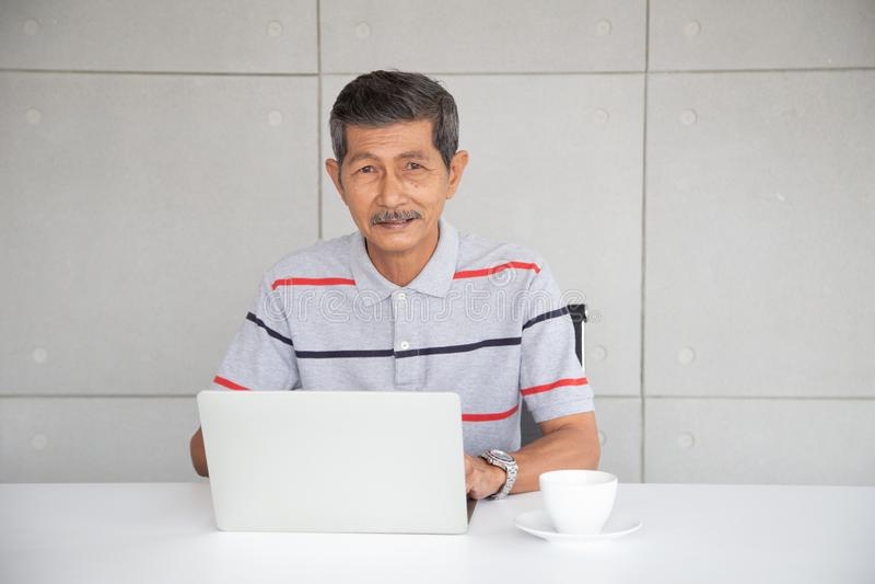 在偶然工作的资深亚洲商人在用途膝上型计算机旁边 免版税库存图片