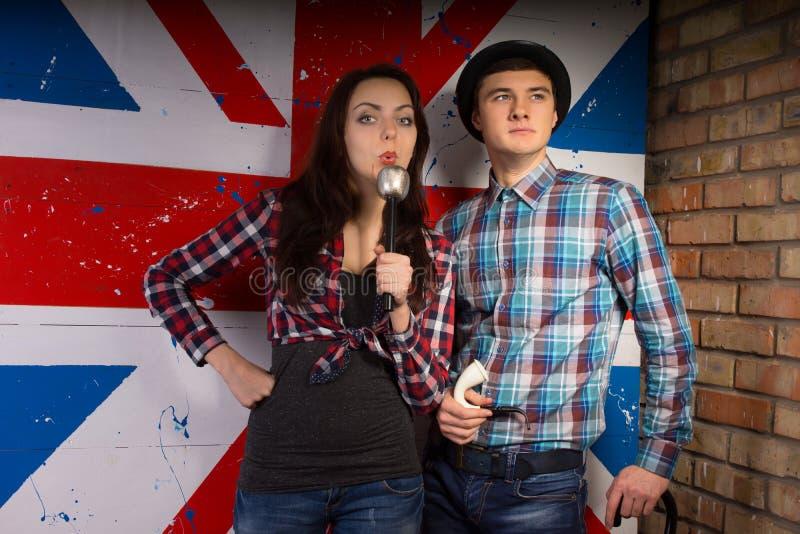 在偶然成套装备的年轻夫妇在前面英国旗子 免版税库存照片