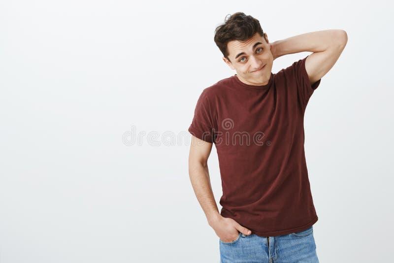 在偶然红色T恤杉的,抓脖子和看从的有罪窘迫欧洲男性模型室内射击 免版税库存照片