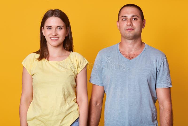 在偶然T恤杉打扮的快乐的年轻女人和人画象,看和微笑直接地照相机 愉快的夫妇消费 免版税库存照片