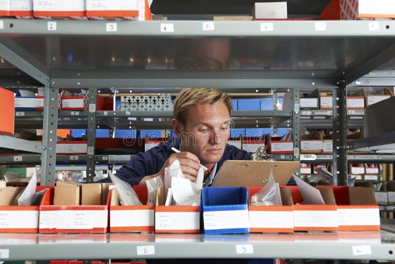 在储藏室检查股票的工厂劳工 免版税库存照片