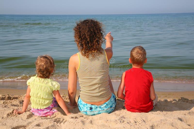 在儿童母亲之后的海滩 免版税图库摄影