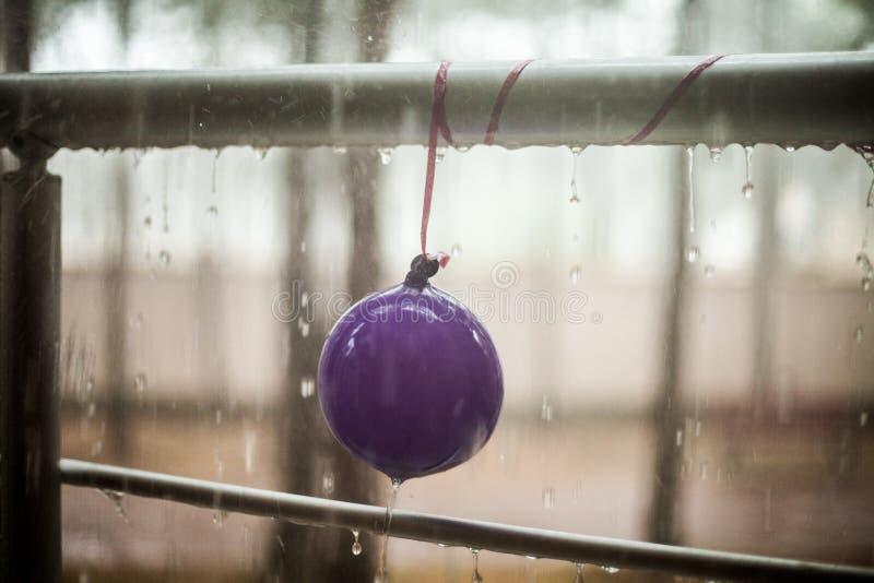 在儿童气球和金属扶手栏杆,夏天雨的小滴 免版税库存照片