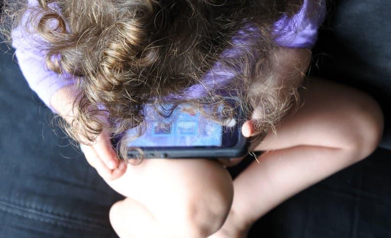在儿童游戏的看法上在手机的 免版税库存照片