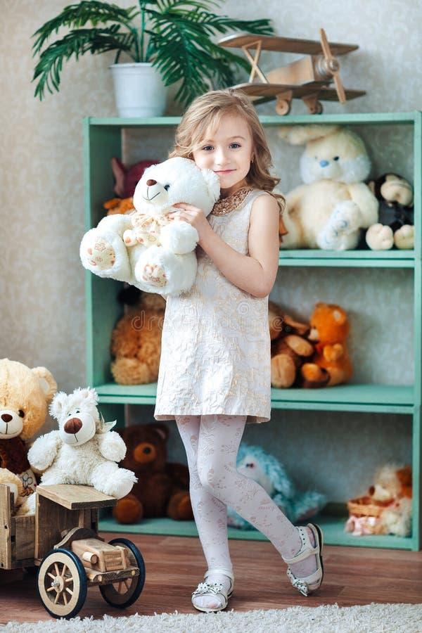 在儿童` s屋子内部,小白肤金发的女孩拿着一头北极熊 免版税库存照片