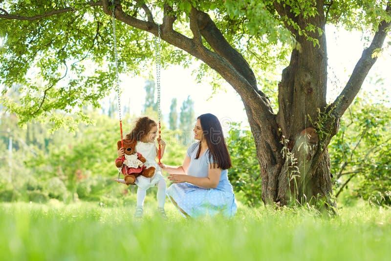 在儿童` s的妈妈卷在公园摇摆在夏天 免版税库存照片