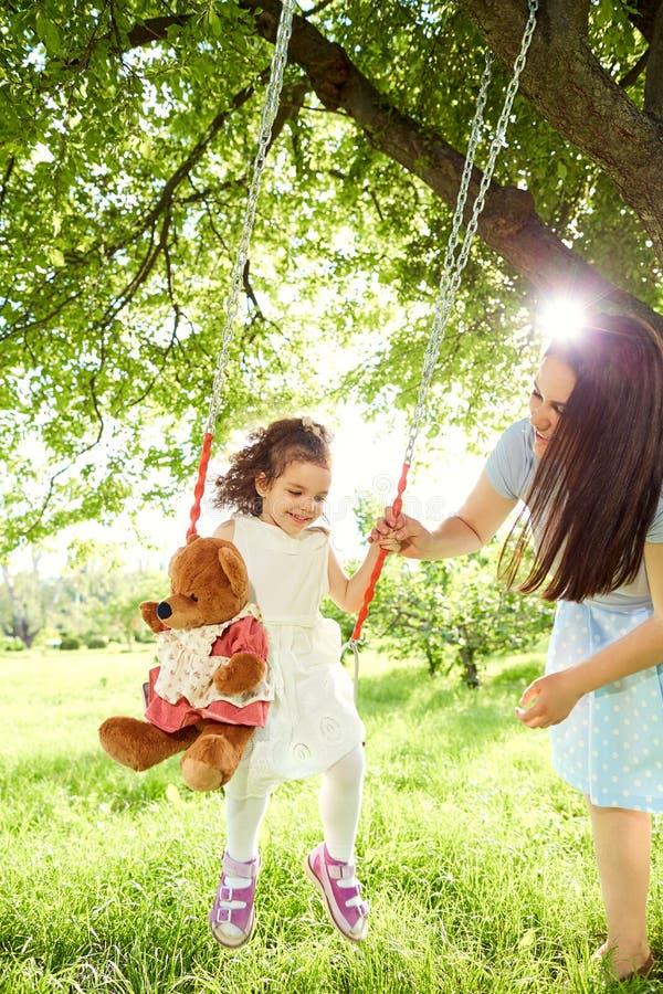 在儿童` s的妈妈卷在公园摇摆在夏天 免版税图库摄影