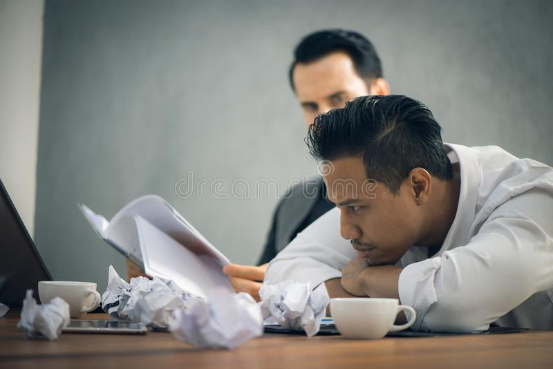 在充分坐在办公桌的黑暗的衣服的担心的商人有被超载与工作的书和纸的 库存照片