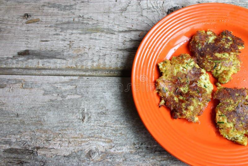 在充分木表上的橙色板材花椰菜和硬花甘蓝薄煎饼 免版税库存图片