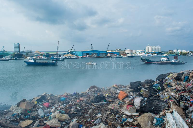 在充分海景的垃圾堆烟、废弃物、塑料瓶、垃圾和垃圾附近在Thilafushi地方热带海岛 免版税库存图片