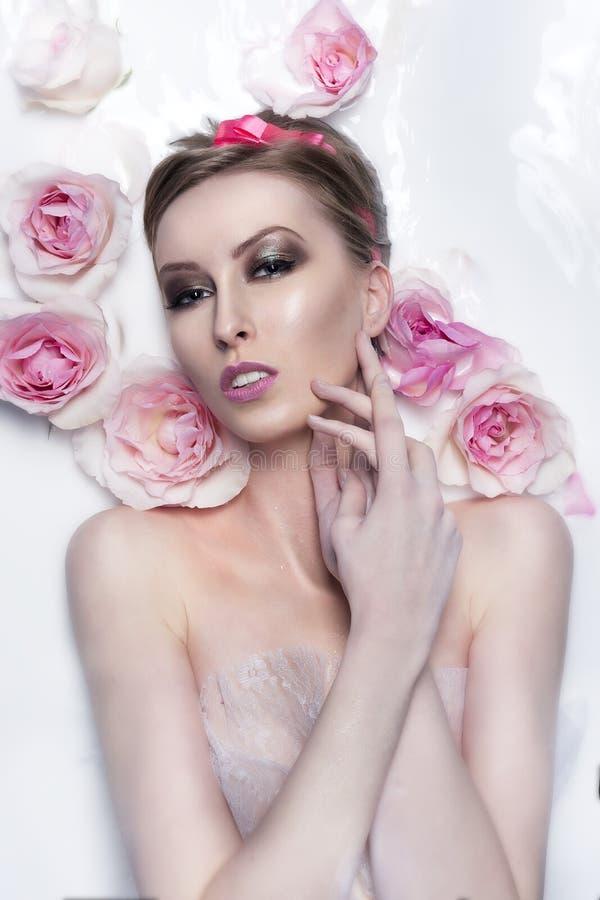 在充分温泉浴缸的女孩` s画象与玫瑰花的牛奶  免版税库存图片
