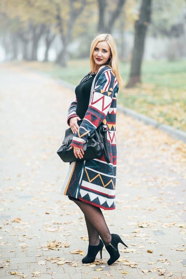 在充分的成长的画象,黑礼服的可爱的年轻白肤金发的妇女走在秋天公园的 图库摄影