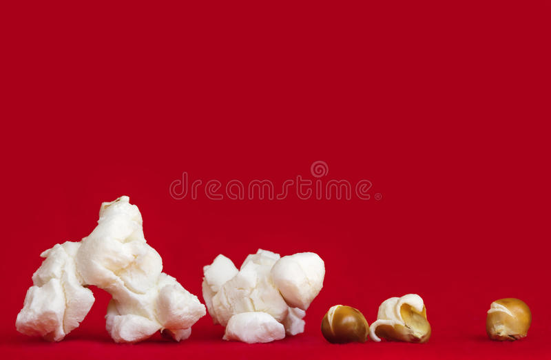 在充满活力的红色背景流行的和Unpopped仁的玉米花 免版税库存图片