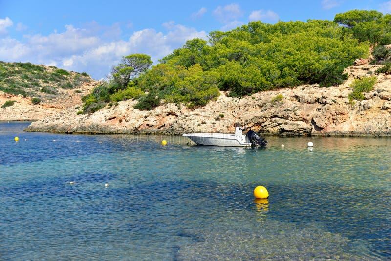 在光亮的水晶绿松石的偏僻的小船浇灌在洞海滩在Portinatx,伊维萨岛 免版税库存图片
