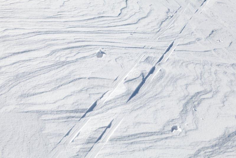 在光亮的随风飘飞的雪之上的雪和滑雪轨道 免版税图库摄影