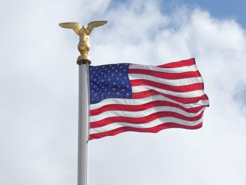 在光和风的美国国旗与多云天空在背景中 库存照片