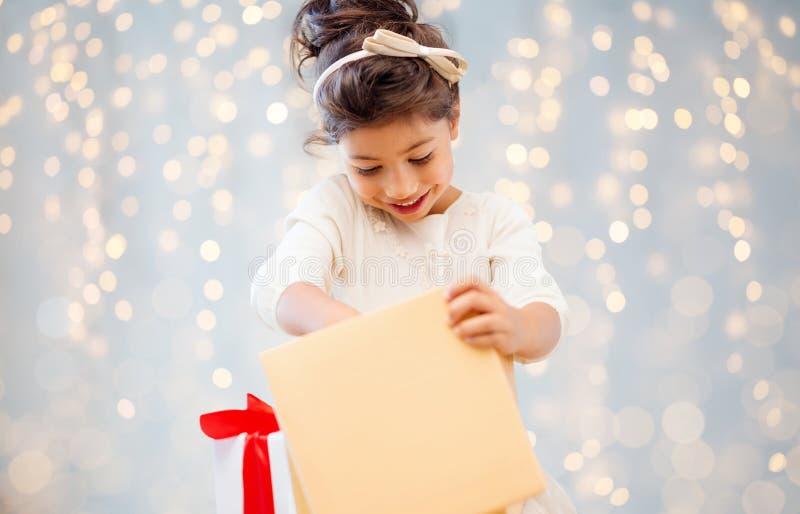在光的微笑的小女孩开头礼物盒 免版税库存照片