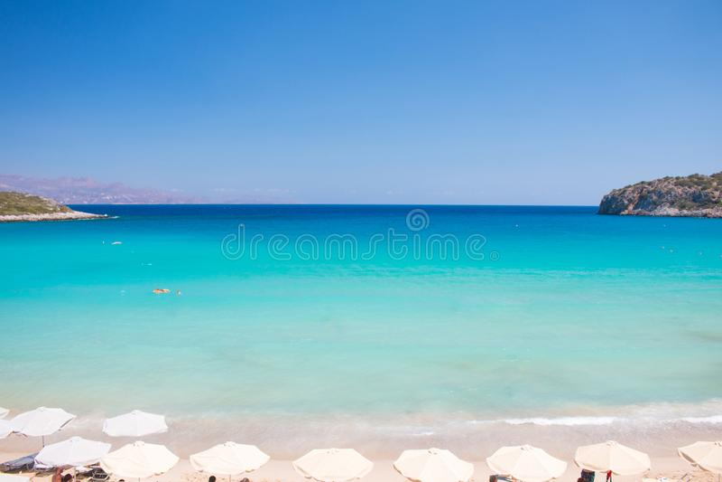 在克利特海岛,希腊的美丽的五颜六色的海滩 Voulisma与伞和sunbeds的天堂海滩 暑假旅行holid 免版税库存图片