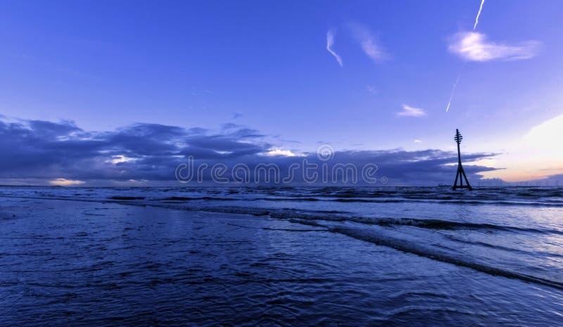在克罗斯比海滩在冬天,克罗斯比,利物浦,英国的日落 免版税库存照片