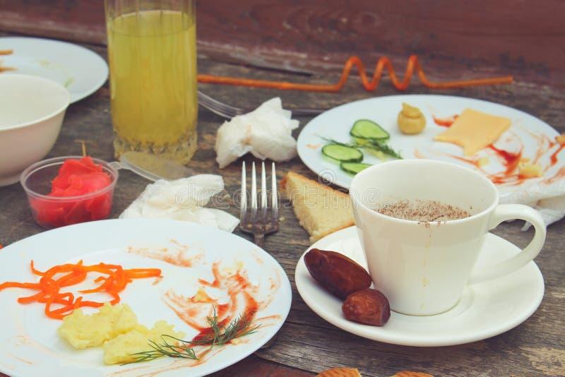 在党以后的杂乱桌 残余食物,溢出的饮料,肮脏的盘 图库摄影