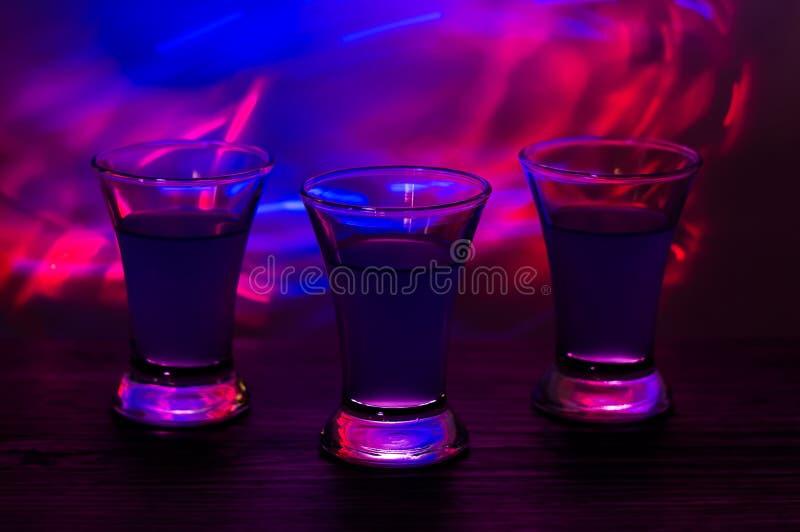 在党的三份饮料 与鸡尾酒的三射击在酒吧 酒,伏特加酒,新鲜 发光在色的背景 夜clu 免版税图库摄影